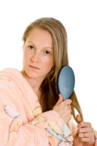 Woman brushing hair and worrying