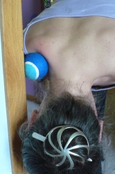 Self massage techniques: using a tennis ball against a door frame for trapezius massage